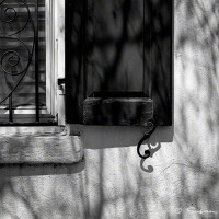 shadows on vintage building with black shutters