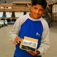 Cusco boy displays Macchu Picho postcards