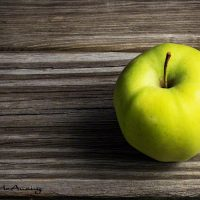 Single green apple on weathered wood.