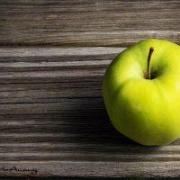 Single green apple on weathered wood.