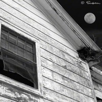 black and white photo of weathered home with full moon rising.