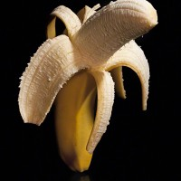 banana partially peeled on black